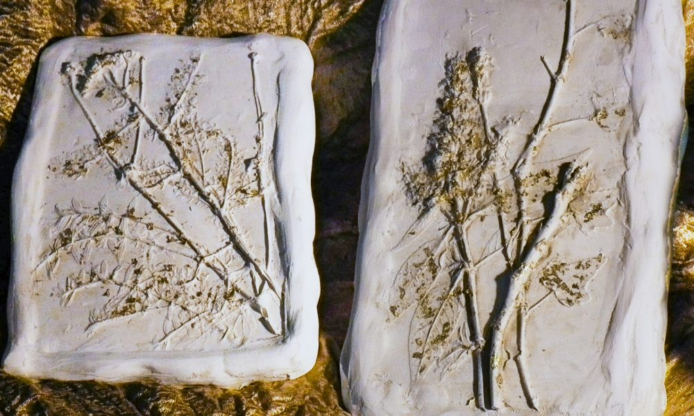 impressions of leaves in clay with gold glitter